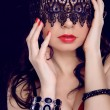 Sexy beautiful woman with black lace pattern on eyes and red lip — Stock Photo #22761140