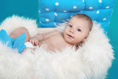 Close-up of lovely baby boy resting on fur bed over blue backgr — Stock Photo