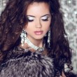 Beautiful woman with long brown hair in luxury fur coat. Closeup — Stock Photo #23295702