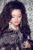 Beautiful woman with long brown hair in luxury fur coat. Closeup — Stock Photo