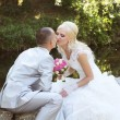 Bride and groom embrace and kissing on their wedding day — Stock Photo