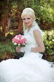 Mooie bruid met boeket van bloemen, portret buitenshuis — Stockfoto
