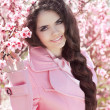 Beautiful brunette girl with braided hair over pink blossom tree — 图库照片