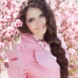 Beautiful brunette girl with braided hair over pink blossom tree — Stok fotoğraf