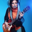 Rock girl plating on electric guitar isolated on blue background — Stock Photo