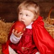 Little girl is sitting on pile of straw eating apple. Little Red — Stock Photo #24606639