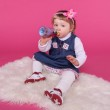 Portrait of funny little girl drinking water sitting on fur over — Stock Photo #24606653
