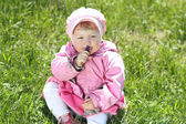 Portrait of happy little girl resting on green grass in the park — Stock Photo