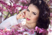 Beautiful brunette woman over pink brunch of tree, outdoors port — Stock Photo
