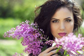 Young brunette woman with lilac flowers, Outdoors portrait — Stock Photo