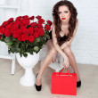 Beautiful young woman with bouquet of red roses and gift box, Va — Stockfoto