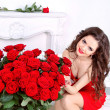 Beautiful smiling woman with red roses flowers bouquet in modern — Stock Photo #24747649