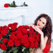 Beautiful brunette woman with red roses flowers bouquet in moder — Stock Photo