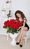 Hermosa joven con ramo de rosas rojas en moderno interi — Foto de Stock