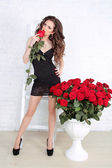 Sexy brunette woman with Red roses at home interior apartment — Stock Photo