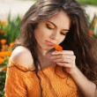 Beautiful brunette woman with colored makeup smelling flower, ov — Stock Photo #25306261