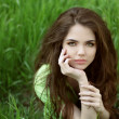 Young brunette woman on the green field grass, outdoors portrait — Stock Photo