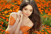 Young woman outdoors portrait over orange marigold flowers — Stock Photo