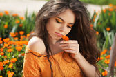 Beautiful brunette woman with colored makeup smelling flower, ov — Stock Photo