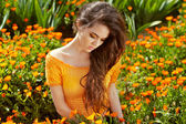 Healthy Long Curly Hair. Beautiful Brunette Woman over marigold — Stock Photo