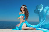 Beautiful woman model in Blowing Dress Flying resting over blue — Stock Photo