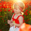 Smiling little girl in red poppies filed, sunset. Outdoors portr - Stock fotografie