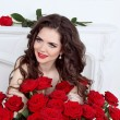 Beautiful brunette woman with bouquet of many red roses flowers — Stock Photo
