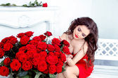 Beautiful brunette woman with red roses bouquet flowers at inter — Stock fotografie