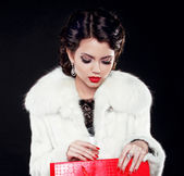 Fashion model woman in fur coat open shopping bag. Isolated on b — Stock Photo