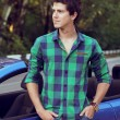 Stock Photo: Handsome man with casual clothes posing near his car, outdoors p