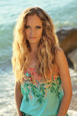 Beautiful woman with wavy hair on sea beach background, outdoors — Stock Photo