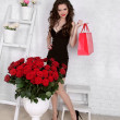 Beautiful young woman with bouquet of red roses and gift box, Va — Stock Photo