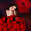 Stock Photo: Young beautiful woman with red roses bouquet over flowers