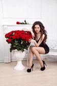 Sexy beautiful woman with red roses bouquet in interior apartmen — Stock Photo