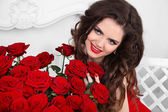Coquette Girl. Beautiful happy woman with bouquet of many red ro — Stockfoto