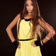 Beautiful young woman posing in yellow dress isolated on black b — Stock Photo