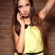 Beautiful young woman posing in yellow dress over brick wall — Stock Photo