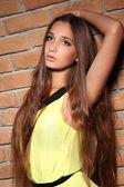 Fashion portrait of beautiful woman model leaning on brick wall — Stock Photo