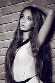 Portret moda model piękna kobieta, opierając się na mur z cegły, — Zdjęcie stockowe