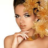 Krásná dívka se zlatými květy. krása modelu ženská tvář. za — Stock fotografie