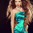 Beautiful elegant woman with long curly hairs in elegant dress p — Stock Photo