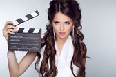 Beautiful brunette woman holding Clapper Board against a grey ba — Stock Photo