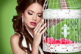 Portrait sexy woman with vintage bird cage isolated on green bac — Stock Photo