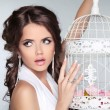Concept photo of amazed woman holding vintage bird cage isolated — Stock Photo