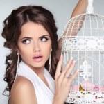 Concept photo of amazed woman holding vintage bird cage isolated — Stock Photo