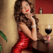 Stock Photo: Rich slim beautiful girl resting sitting at the table holding vi