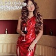 Rich slim beautiful girl holding vine glass posing in red dress — Stock Photo