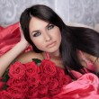 Beauty portrait. Amazing brunette woman with Red Roses lying on — Stock Photo