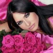 Beauty portrait of brunette girl with pink Roses lying on the be — Stock Photo