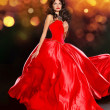 Beautiful brunette wearing in luxury red dress over dark golden — Stock Photo #36719943